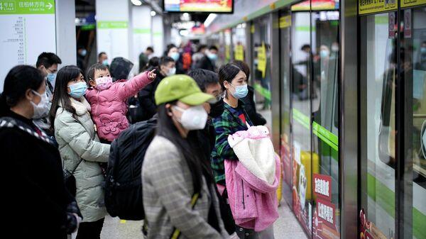Пассажиры в защитных масках на одной из станций метро в Ухани, КНР. 28 марта 2020