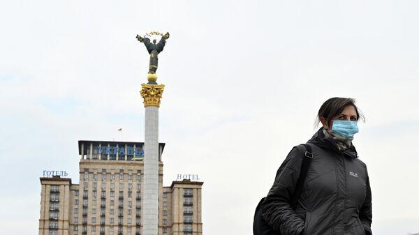 Женщина в медицинской маске на улице Киева