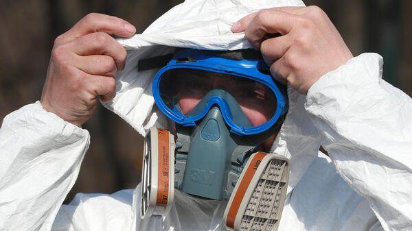 Сотрудник ГБУ Жилищник района Вешняки надевает защитный костюм перед проведением дезинфекции парковой территории от коронавирусной инфекции