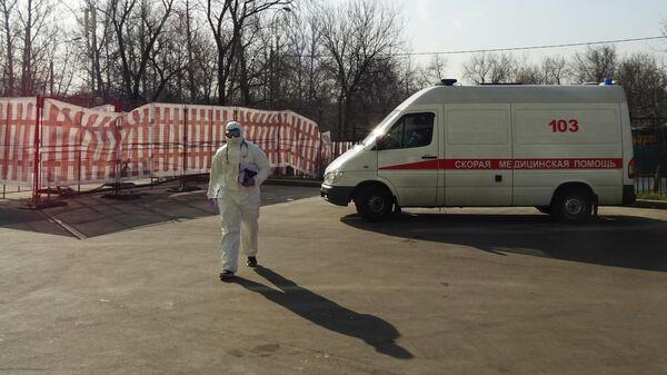 Работник скорой помощи, одетый в защитный костюм, на территории Городской клинической больницы №67