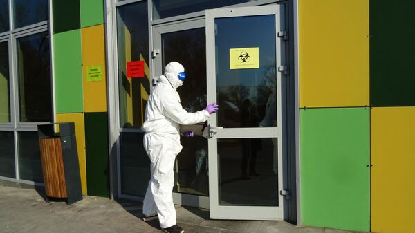 Врач в защитном костюме у входа в отделение перинатального центра Городской клинической больницы №67