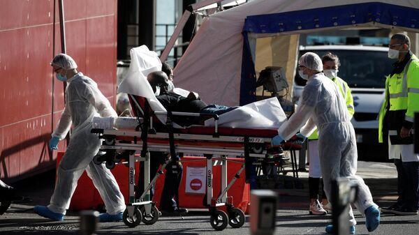 Медработники перевозят пациента на носилках в больнице Анри Мондора в Кретее, недалеко от Парижа