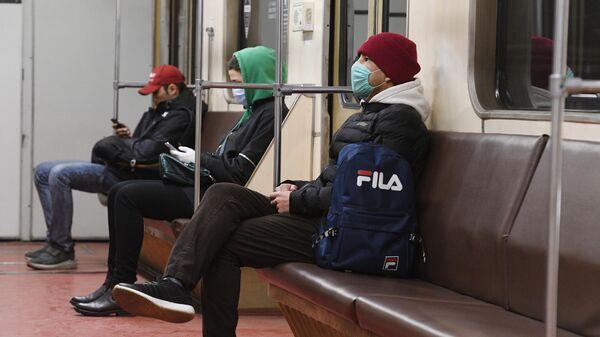 Пассажиры в медицинских масках в вагоне метро в Москве