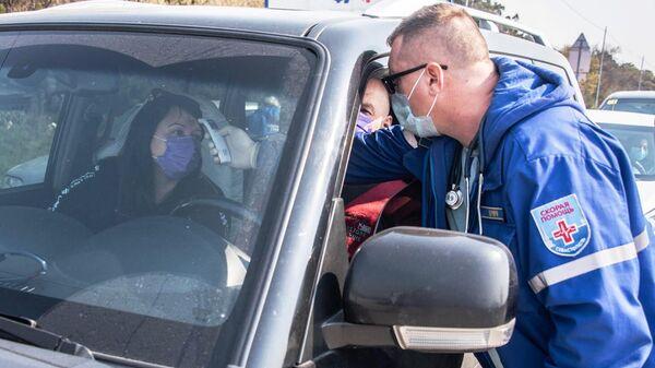 Фельдшер скорой помощи измеряет температуры на блокпосту Мыс Сарыч на 45-м километре Ялтинской трассы
