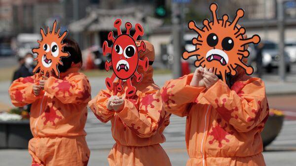 Активисты в масках с изображением коронавируса во время акции в Сеуле, Южная Корея