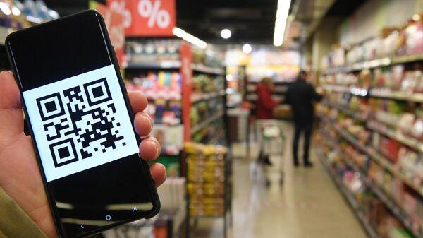 Человек держит смартфон с изображением QR-кода