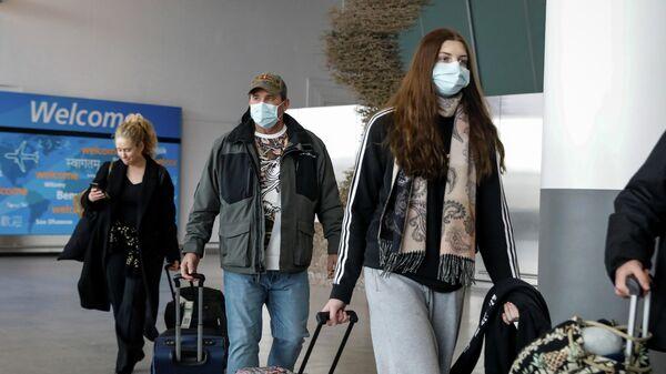 Пассажиры в аэропорту имени Джона Кеннеди в Нью-Йорке, США