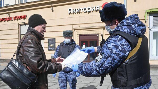 Сотрудники Росгвардии во время раздачи горожанам памяток по профилактике коронавирусной инфекции на одной из улиц в Москве