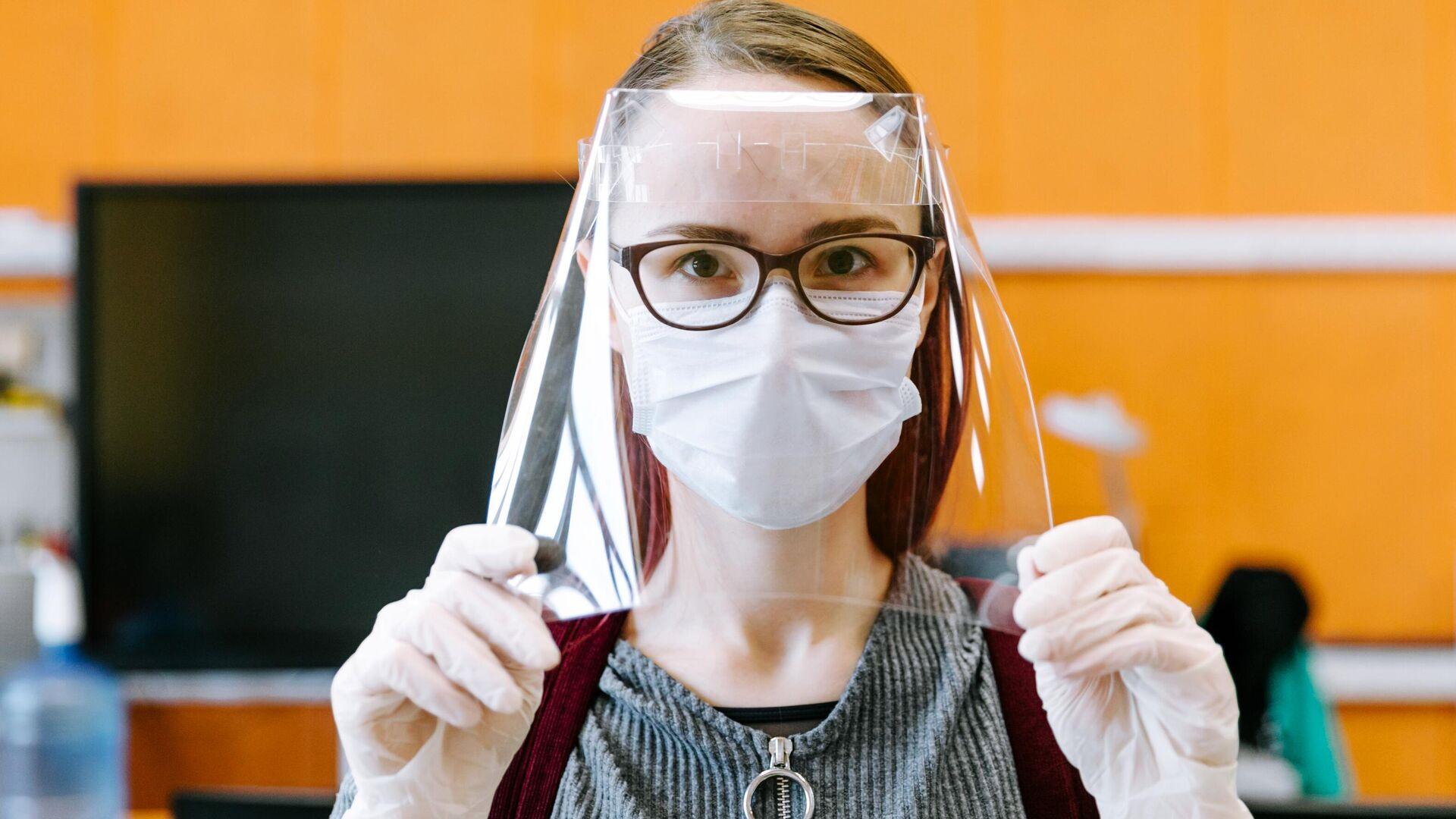 Девушка демонстрирует готовый лицевой экран для индивидуальной защиты глаз, дыхательных путей и лица медицинских работников в технопарке Кванториум. Новатория - РИА Новости, 1920, 16.10.2020