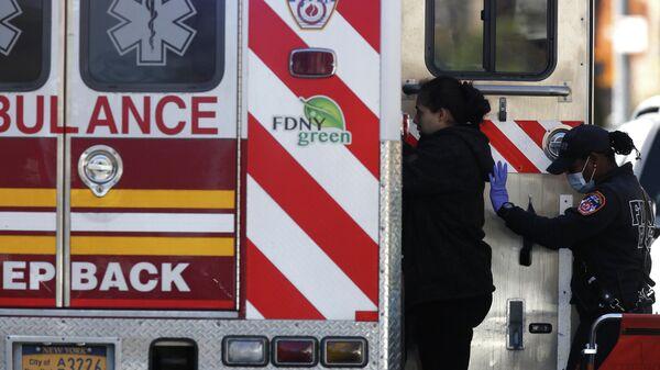 Сотрудница неотложной медицинской помощи Департамента пожарной охраны Нью-Йорка помогает пациентке сесть в машину скорой помощи