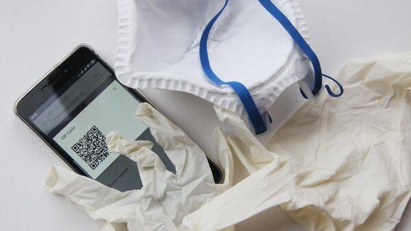 Перчатки, маска и смартфон с QR-кодом для предъявления сотруднику полиции при проверке режима самоизоляци