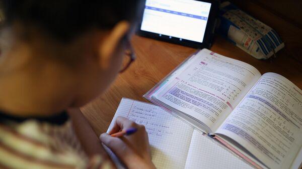 Школьница во время дистанционного обучения дома