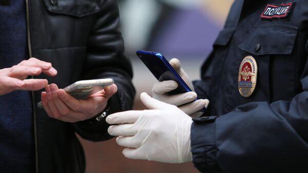 Сотрудник полиции проверяет смартфон с QR-кодом у жителя Нижегородской области
