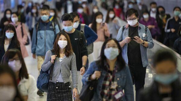 Жители на переходе одной из станций метро в Гонконге
