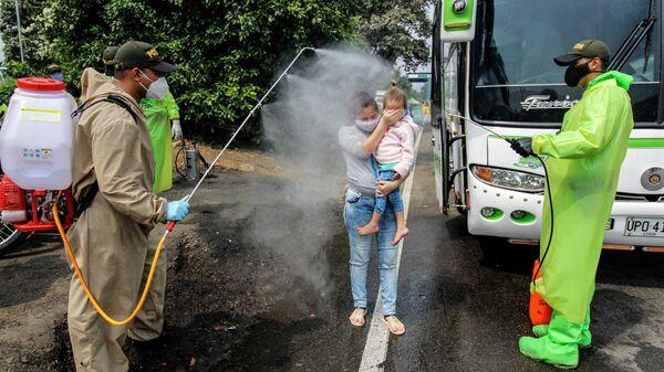 Сотрудники Национальной полиции проводят дезинфекцию граждан Венесуэлы, возвращающихся в страну из Колумбии, в качестве превентивной меры против распространения коронавируса
