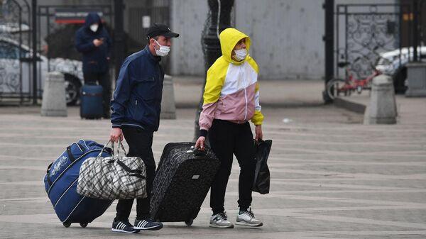 Пассажиры идут на один из вокзалов на Комсомольской площади в Москве