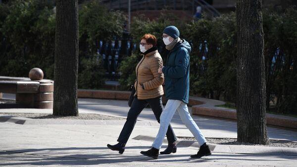 Жители Минска идут по улице в защитных масках