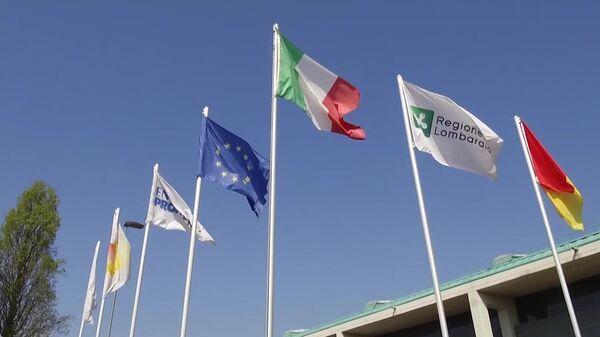 Флаги у полевого госпиталя в Бергамо, в котором российские и итальянские специалисты в круглосуточном режиме будут принимать, диагностировать и лечить заболевших коронавирусом COVID-19