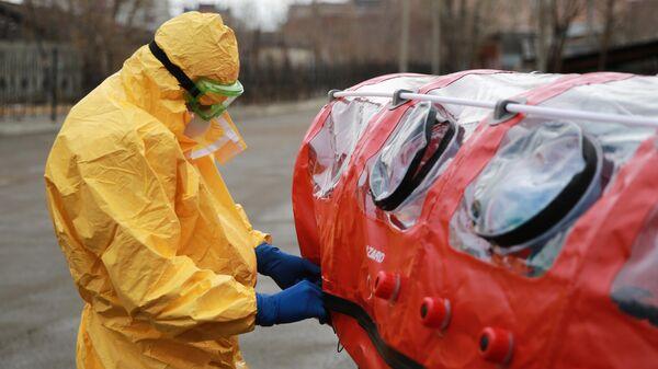 Врач бригады скорой помощи в защитном костюме готовит бокс для перевозки зараженных коронавирусом