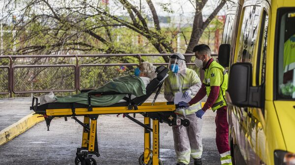 Медицинские работники доставляют пациента на каталке в приемное отделение госпиталя Северо Очоа в Мадриде