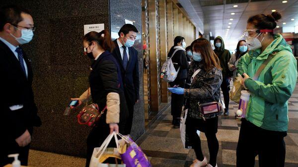 Сотрудники торгового центра проверяют QR-коды на вход в магазин у покупателей