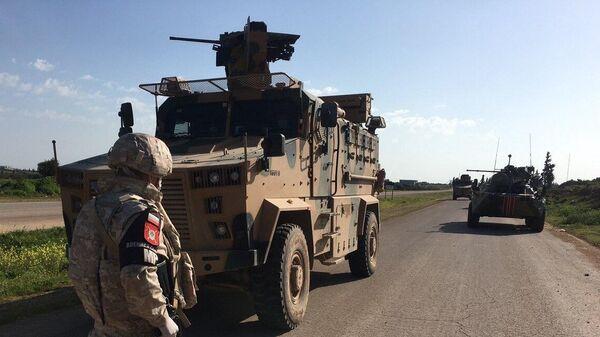 Военнослужащий российской военной полиции во время совместного с турецкими военными патрулирования трассы М-4 в провинции Идлиб в Сирии