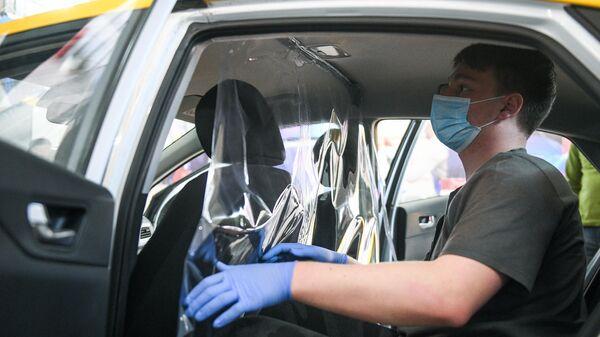 Сотрудник сервиса заказа такси Ситимобил устанавливает в автомобиле защитную перегородку между водителем и пассажиром