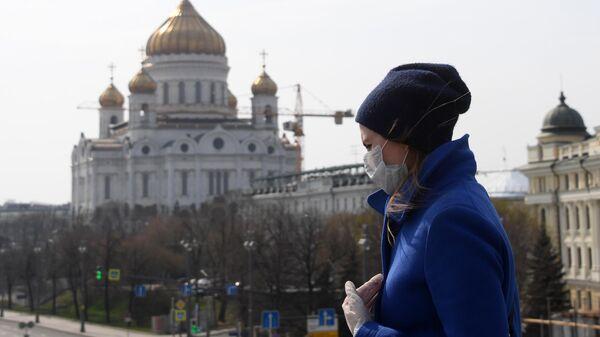 Девушка в защитной маске и перчатках на фоне Храма Христа Спасителя, закрытого для посещения