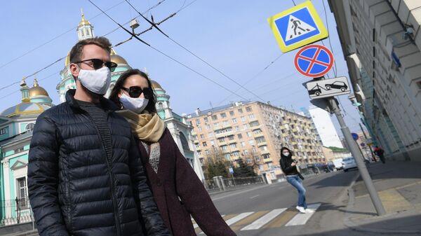 Молодые люди в защитных масках и перчатках на одной из улиц Москвы
