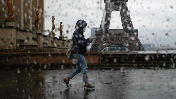 Женщина проходит мимо Эйфелевой башни в Париже во время пандемии вируса COVID-19