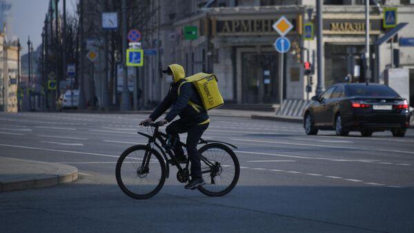Курьер службы доставки Яндекс. Еда едет на велосипеде по Тверской улице в Москве.