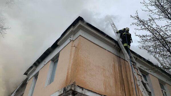 Сотрудник МЧС во время ликвидации пожара на кровле в 2-х этажного здания в Москве