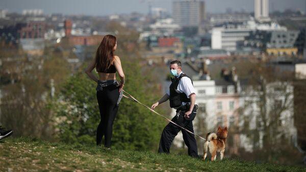 Полицейский в медицинской маске беседует с девушкой, выгуливающей собаку на Примроуз-Хилл Лондон, Великобритания