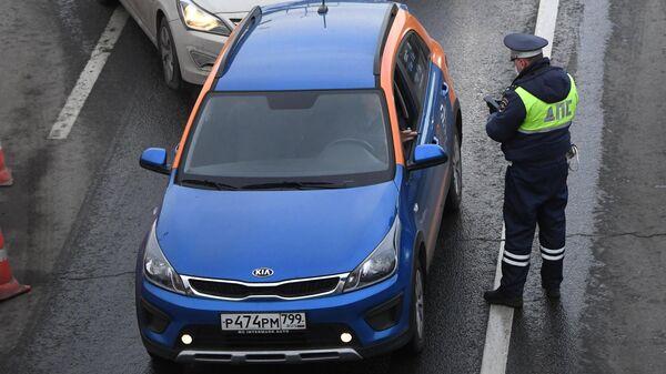 Водитель автомобиля сервиса каршеринга показывает сотруднику ГИБДД на блокпосту при въезде в Москву