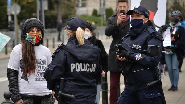 Участники антиправительственной акции и полицейские в Варшаве