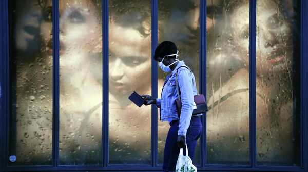 Женщина в защитной маске проходит мимо витрины магазина в Париже