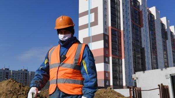 Рабочий в медицинской маске на строительстве жилого комплекса в Новосибирске