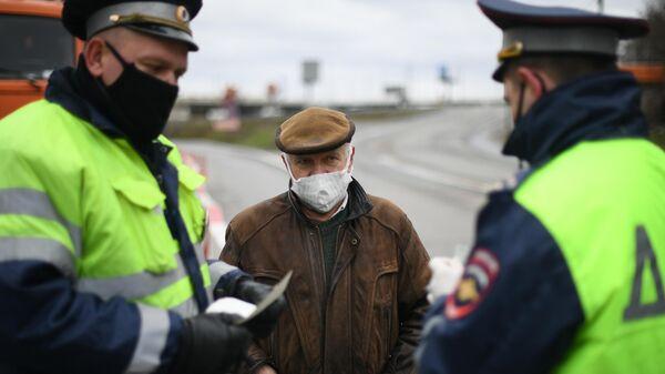Инспекторы дорожно-патрульной службы проверяют у водителя цифровой пропуск на передвижение по Москве