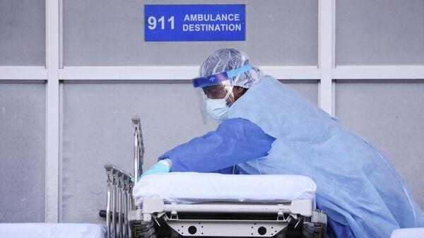 Медицинский работник настраивает тележку со носилками в медицинском центре в Бруклине, Нью-Йорк, США