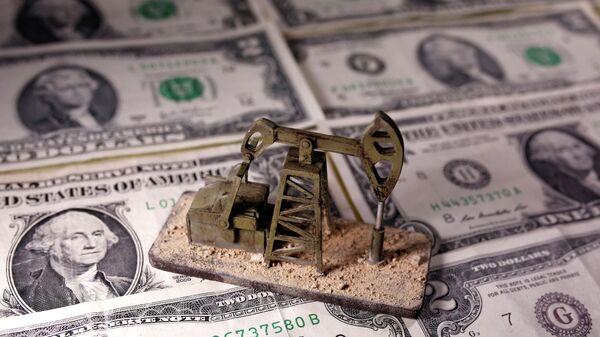 Нефтяной станок-качалка на фоне долларовых банкнот