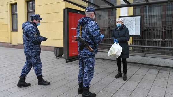 Сотрудники Росгвардии проверяют цифровой пропуск у женщины в Москве