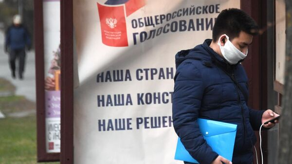 Молодой человек в защитной маске стоит у агитационного плаката