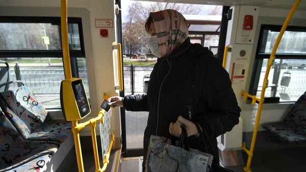 Женщина в защитной маске прикладывает социальную карту москвича к валидатору в салоне городского автобуса в Москве. 22 апреля 2020