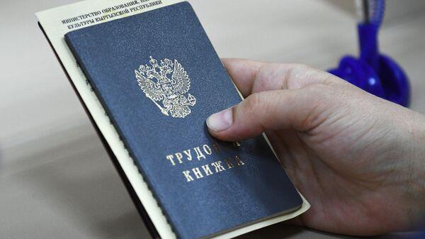 Сотрудница Центра занятости населения Ленинского района в Новосибирске держит в руках документы посетителя