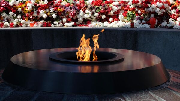 Цветы у Вечного огня Мемориального комплекса Цицернакаберд в Ереване в память о жертвах геноцида армян в Османской империи 1915 года