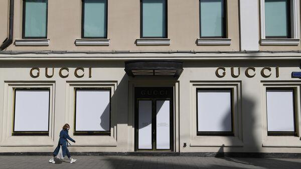 Девушка в защитной маске проходит мимо витрин закрытого магазина Gucci на улице Петровка в Москве