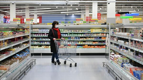 Женщина в защитной маске покупает продукты в гипермаркете