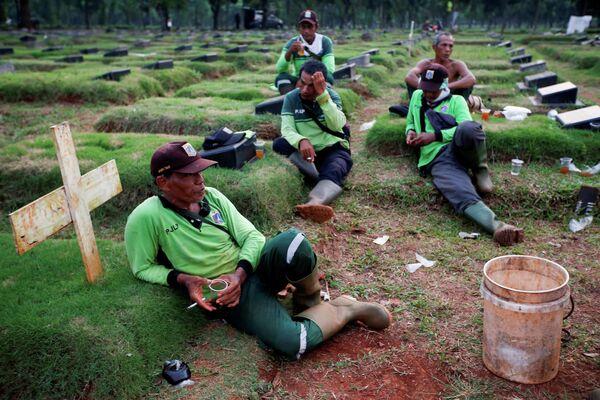 Могильщики отдыхают в перерыве между работой на кладбище в Джакарте, Индонезия