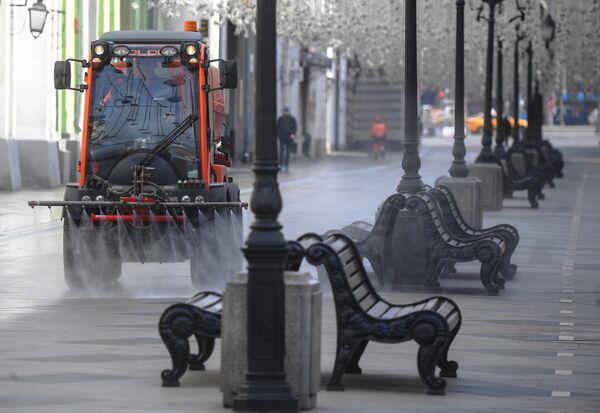 Автомобиль коммунальных служб дезинфицирует дороги и тротуары в центре Москвы