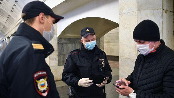 Сотрудники полиции в защитных масках на станции метро  Москвы Охотный ряд проверяют цифровой пропуск у пассажира